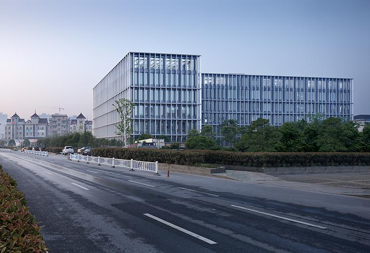 这栋小型办公建筑位于城市边缘区域,周边簇拥着大量风格鲜明的城中村建筑,临近的过境道路从早到晚都彰显着现代物流的繁忙和纷乱。作为新一轮都市更新的先锋,该建筑从概念之初就试图以一种清雅脱俗的方式坐隐于繁杂,以简洁的新现代风格凸显现代办公高效透明的特征。 该建筑共5层,屋顶24m高,以横向展开的方式占据了用地中心区,平面呈横卧7字形,将紧凑的用地划分为动静两宜的南北两个狭长型的庭院。