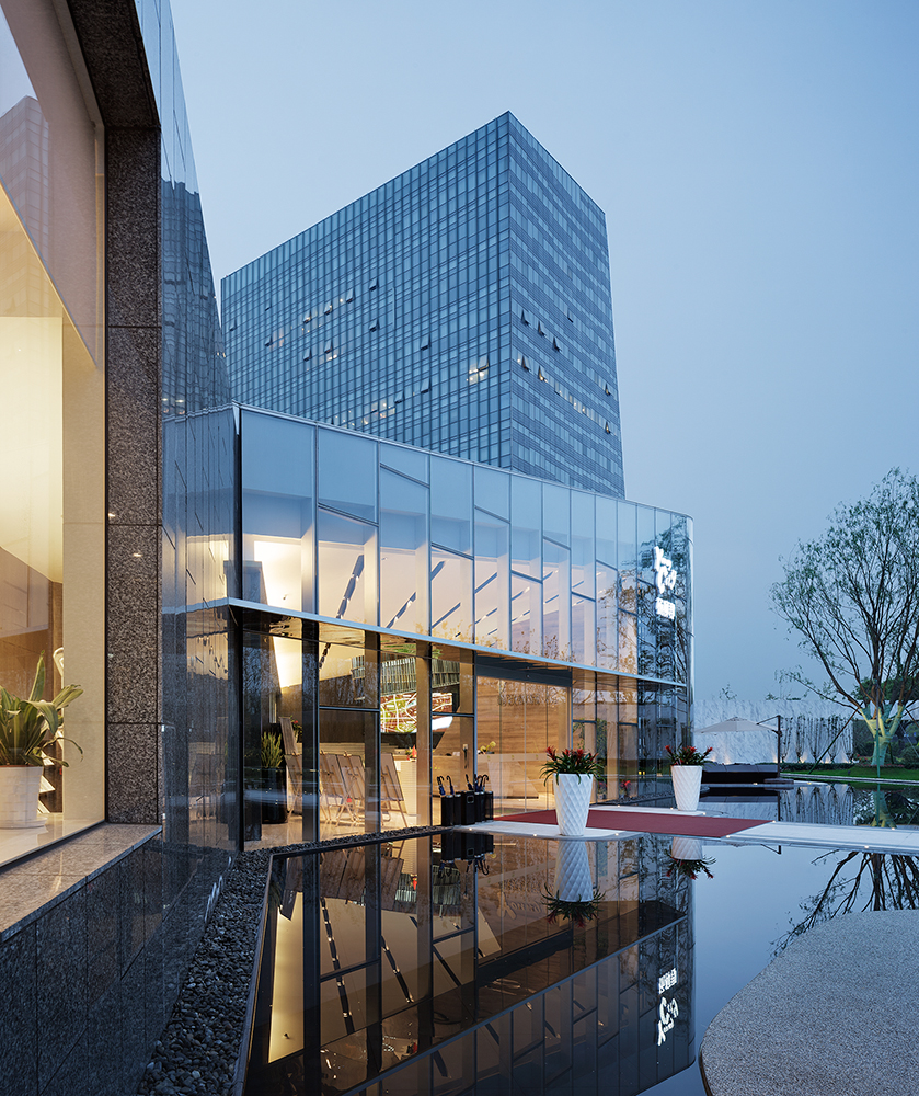 杨柳郡生活体验馆迥异于以往的绿城销售中心,晶莹剔透,就像一颗璀璨的钻石。超大面落地玻璃,将室内的视野全面打通,因为杨柳郡希望生活是没有边界的。gad试图将整体建筑风格显得更为年轻、灵动,又兼顾了室内外场景的自然过渡,整体建筑采用大跨度钢结构建立,在室内很少看到柱体,都是整体与传统意义上的售楼处迥然不同,现代简洁透明的设计灵感在这里重现,构筑一个年轻的休闲生活场所。这与young city的定位充分吻合,为年轻置业者诠释了一种全新的生活态度,让他们在这里找到回家的感觉。玻璃结构将这个建筑体支撑起来,感觉非常